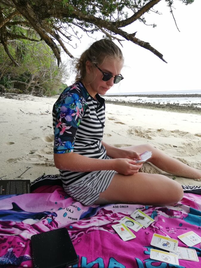 My sister playing card games on holiday mode- sunglasses and sand.