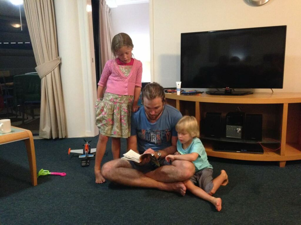Dad reading to two of my siblings, ironically with a TV in the background- switched off, of course.
