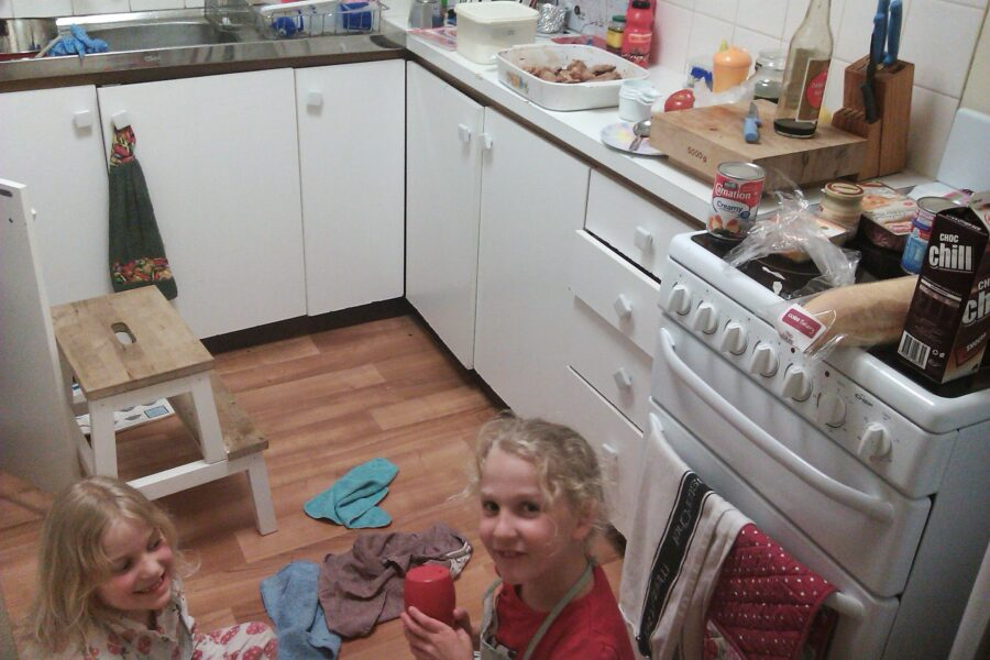 Gabby and I (ages 6 and 7) seated on the floor in the kitchen, surrounded by random kitchen items. A dish of chicken wings is on the bench, with some other random ingredients; chocolate milk, a baguette, condensed milk, mustard, ham.