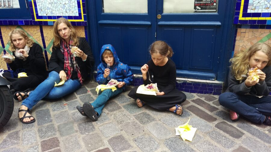 All my family seated on the cobblestone path in front of a closed shop in Paris, eating some of the best falafel I've ever had.